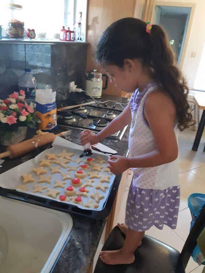 ילדה העוזרת לאמה, הבשלנית המתנדבת, בהכנת עוגיות לקשיש